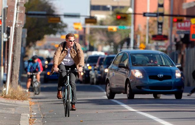 Мужчина едет на велосипеде по дороге