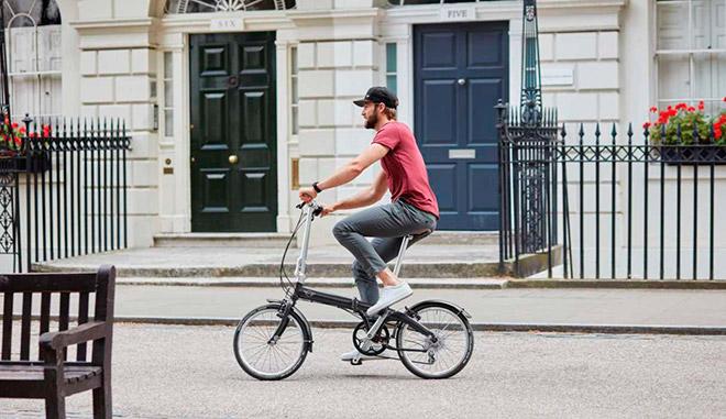Мужчина на складном велосипеде в городе